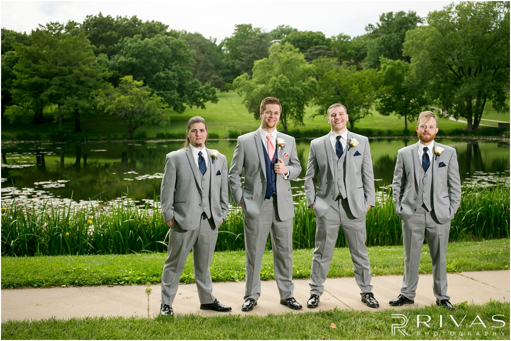 St. John the Evangelist Catholic Church Spring Wedding | A photo of a groom and his groomsmen standing in the grass in front of Potter Lake in Lawrence, KS.