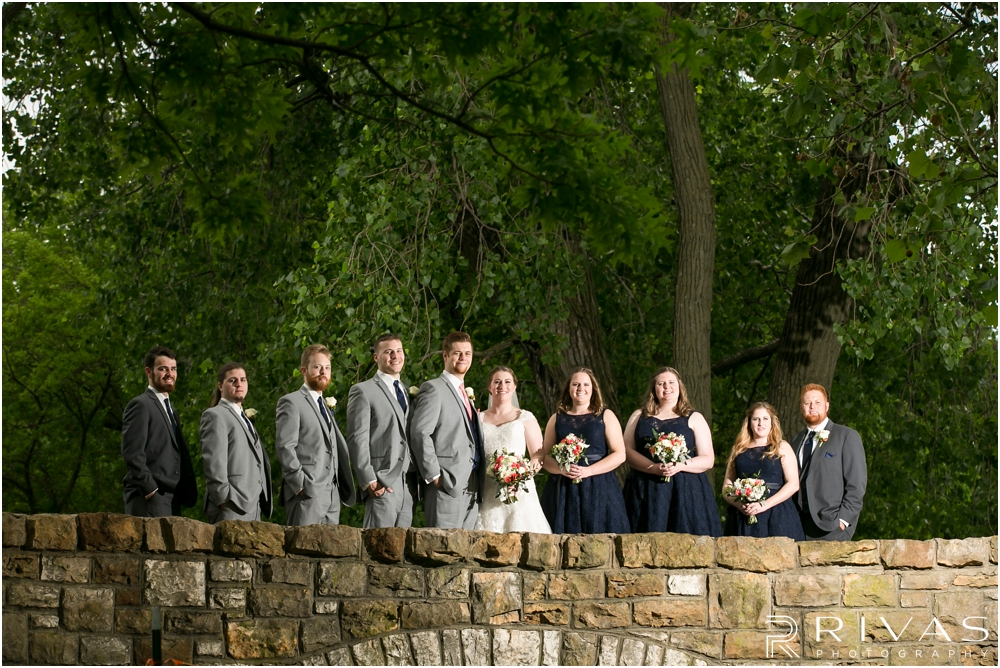 St. John the Evangelist Catholic Church Spring Wedding | A picture of a bride and groom with their wedding party standing on the stone bridge at Potter Lake in Lawrence, KS.