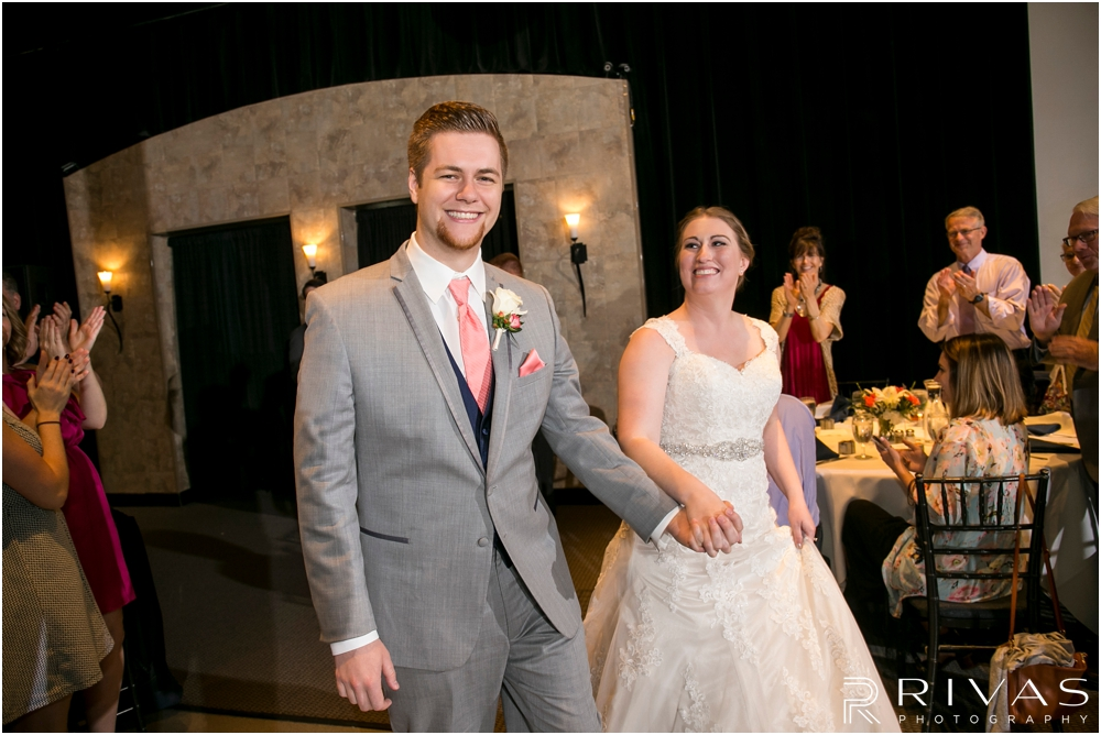 St. John the Evangelist Catholic Church Spring Wedding | A candid image of a bride and groom entering their reception while friends and family cheer and celebrate.