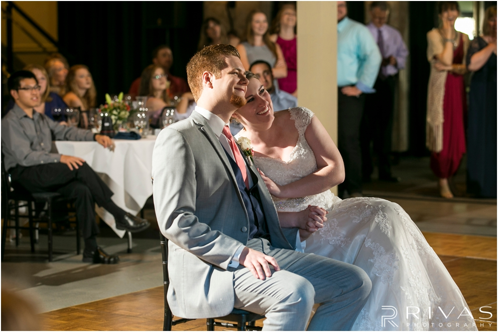 St. John the Evangelist Catholic Church Spring Wedding | A candid photo of a bride and groom enjoying a photo slideshow during their reception.