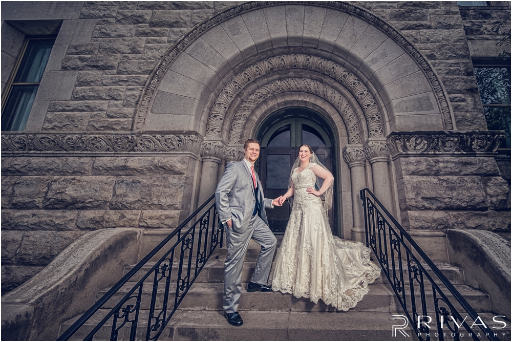 St. John the Evangelist Catholic Church Spring Wedding | A dramatic picture of a bride and groom holding hands, looking at the camera on the courthouse steps in Lawrence, KS.