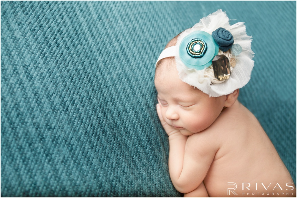 Turquoise Themed Newborn Session | Photo of newborn baby girl laying on turquoise background with large white and turquoise bow.