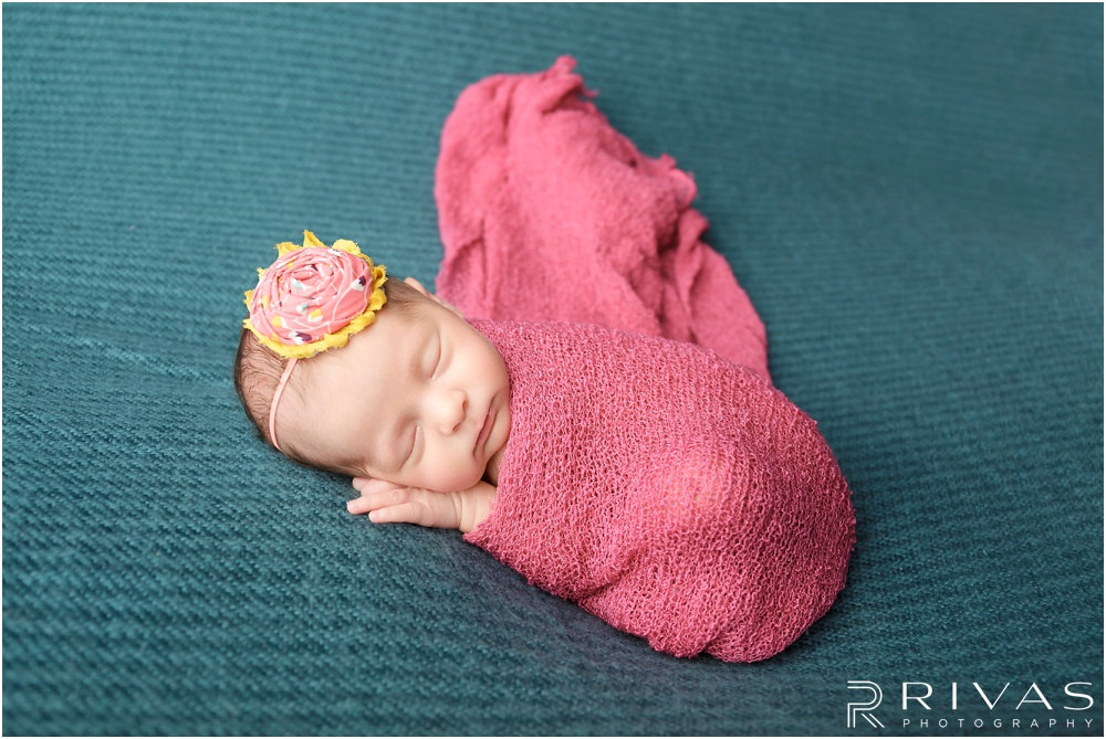 Turquoise Themed Newborn Session | Photo of newborn baby girl laying on turquoise background with pink blanket and pink and yellow bow.