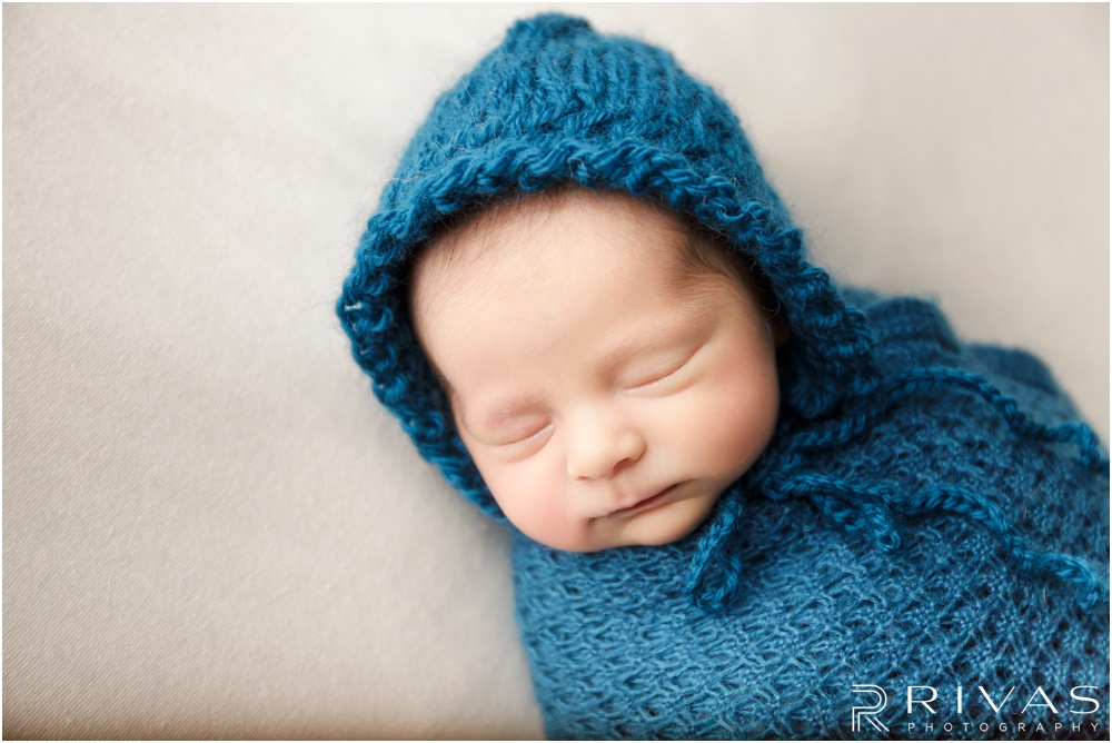 Turquoise Themed Newborn Session | Photo of newborn baby girl wrapped in turquoise wrap on cream backdrop.