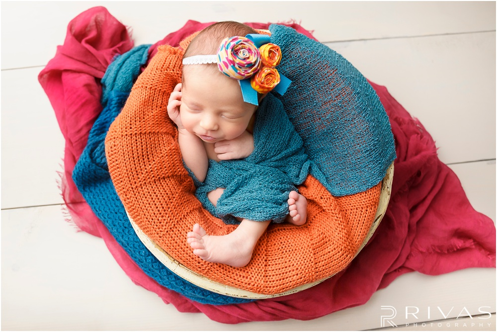 Turquoise Themed Newborn Session | Photo of newborn baby girl in cream bucket wrapped in turquoise blanket on white wood plank flooring.