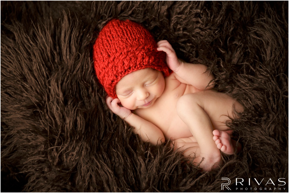 Turquoise Themed Newborn Session | Photo of newborn baby girl with red knit bonnet curled up in brown fur.