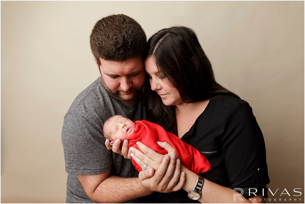 Turquoise Themed Newborn Session | Photo of newborn baby girl wrapped in red with her mom and dad.