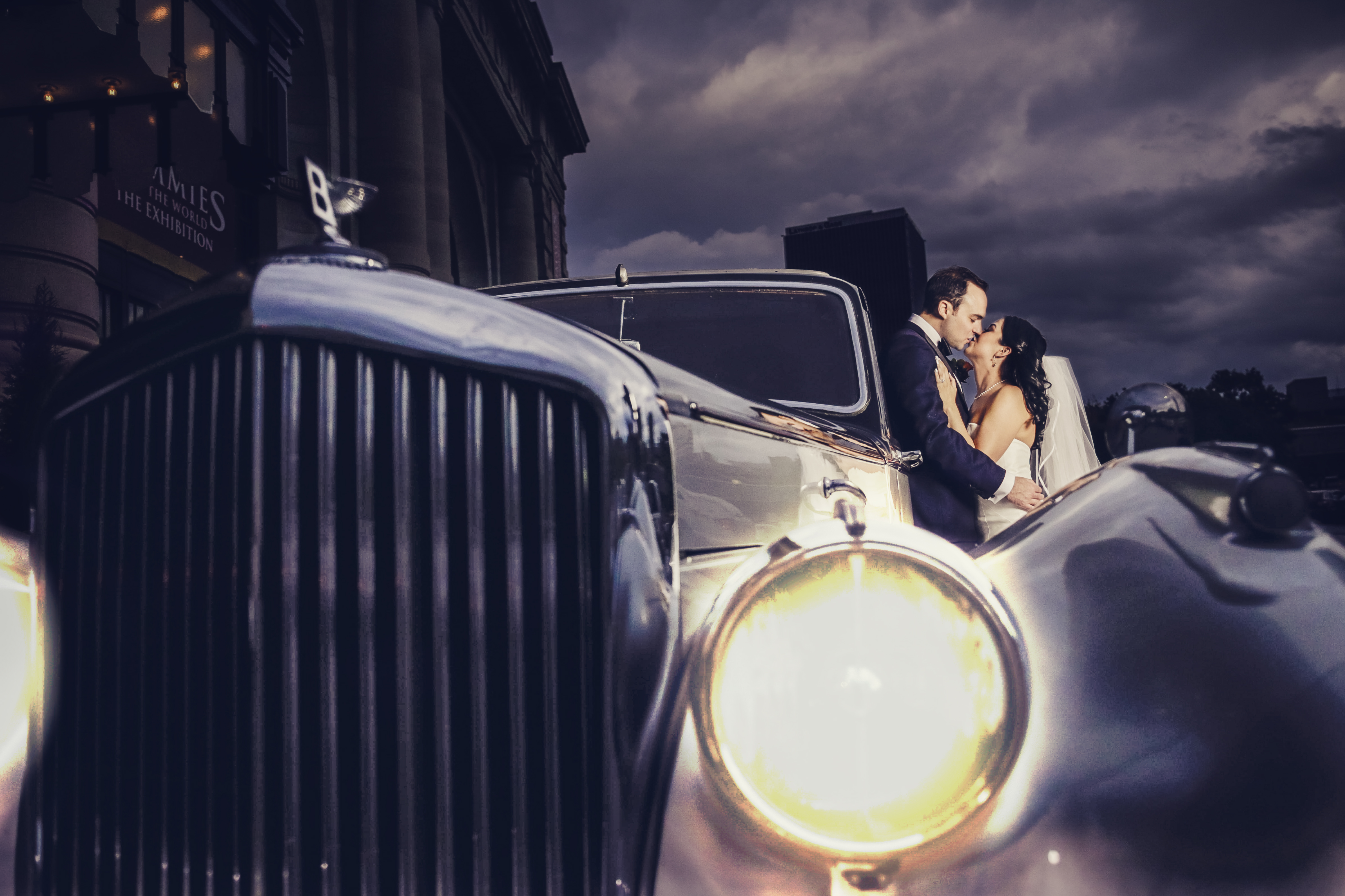 Gatsby Inspired Wedding Sneak Peek | A dramatic photo of a bride and groom sharing a kiss as they lean against a classic car in front of Kansas City's Union Station on their wedding day.