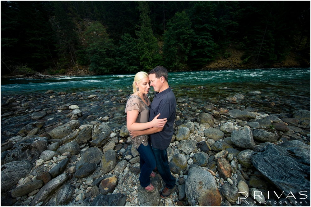 Diablo Lake Engagement Session | A dramatic portrait of an engaged couple embracing on a rocky beach in front of turquoise water at Diablo Lake, Washington.