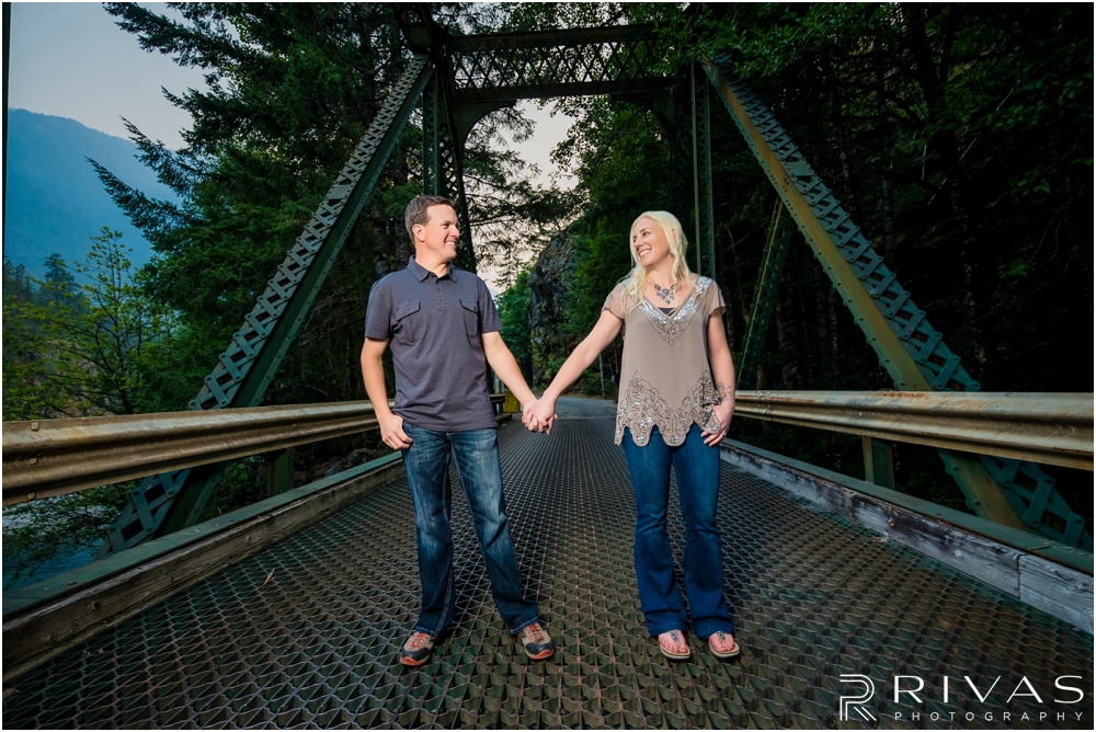 Diablo Lake Engagement Session | A picture of an engaged couple holding hands and standing on an iron bridge at Diablo Lake, Washington.