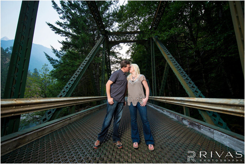 Diablo Lake Engagement Session | A picture of an engaged couple sharing a kiss while standing on an iron bridge at Diablo Lake, Washington.