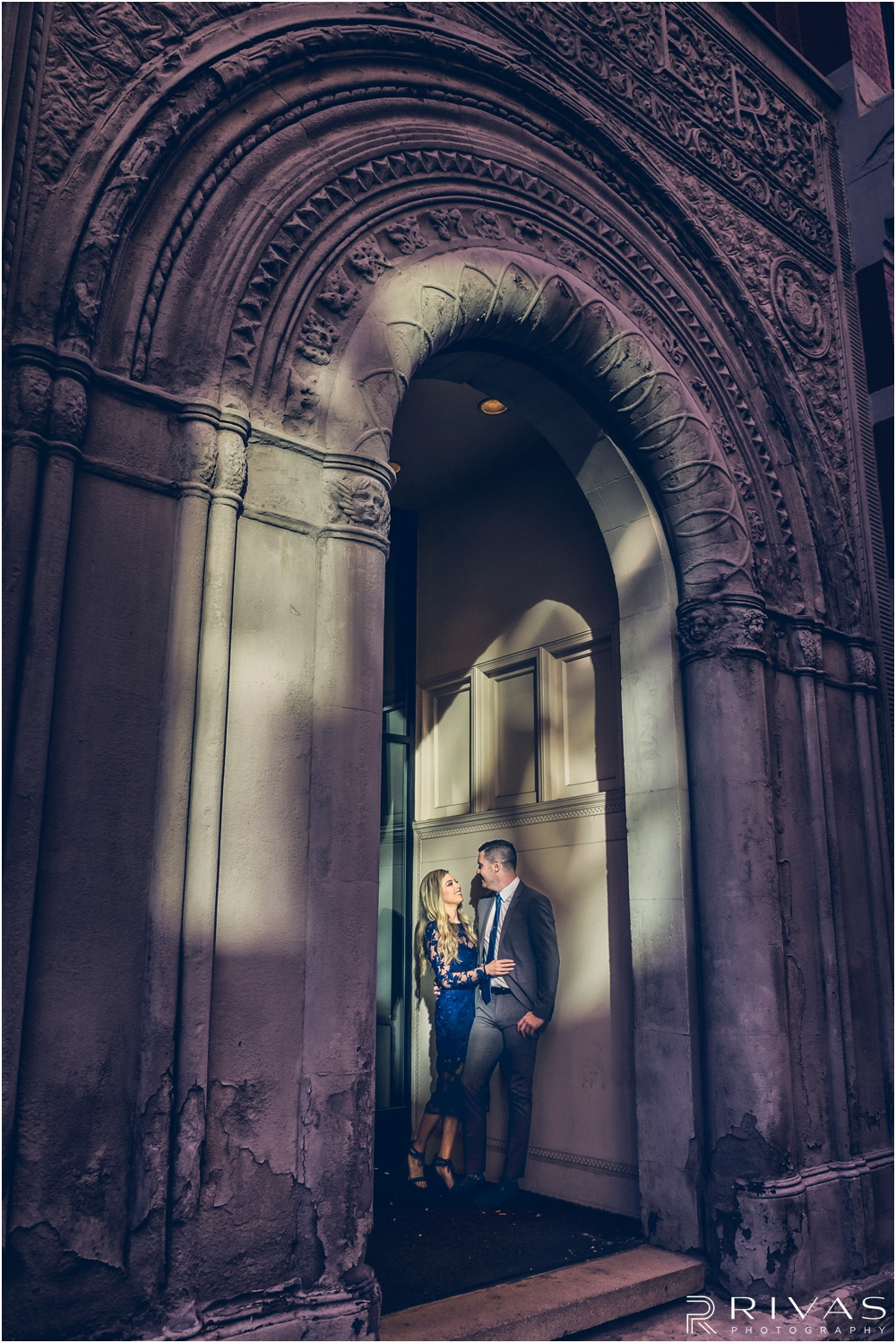 Elegant Downtown KC Engagement Sneak Peek | A moody photo of an engaged couple embracing while standing in a carved alcove with sunlight dancing over them in downtown Kansas City.
