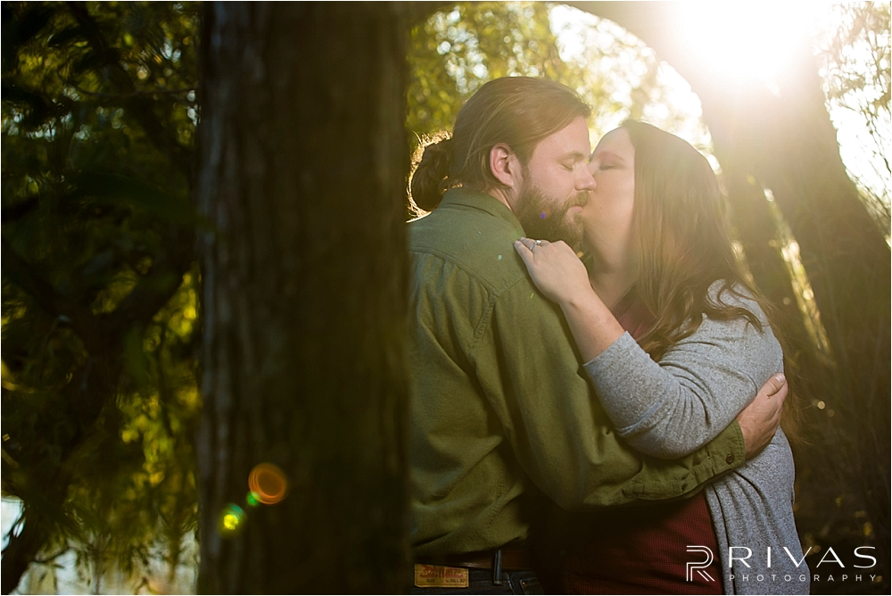 Family Farm Fall Engagement Session | An intimate image of an engaged couple sharing a kiss in the middle of a forest at sunset.