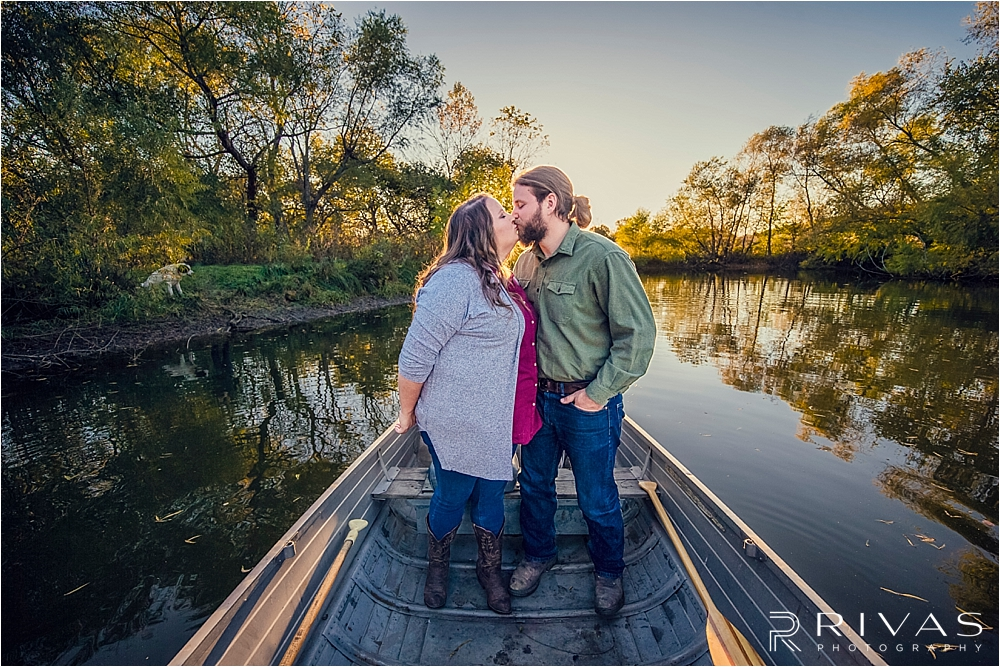 Family Farm Fall Engagement Session | A dramatic picture of an engaged couple standing in a rowboat on a pond surrounded by trees as sun sets.