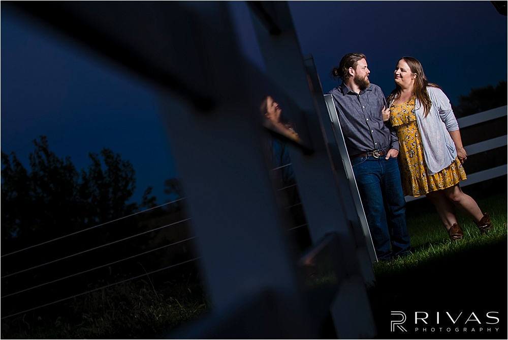 Family Farm Fall Engagement Session | A dramatic portrait of an engaged couple embracing and standing against a white fence after dusk.