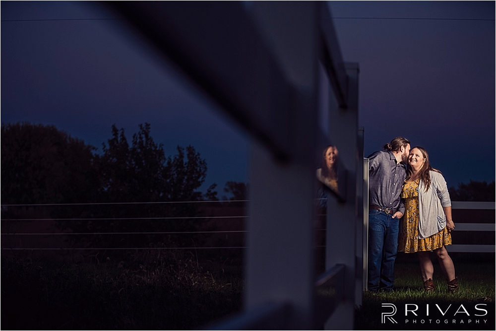 Family Farm Fall Engagement Session | A dramatic portrait of an engaged couple sharing a kiss and standing against a white fence after dusk.