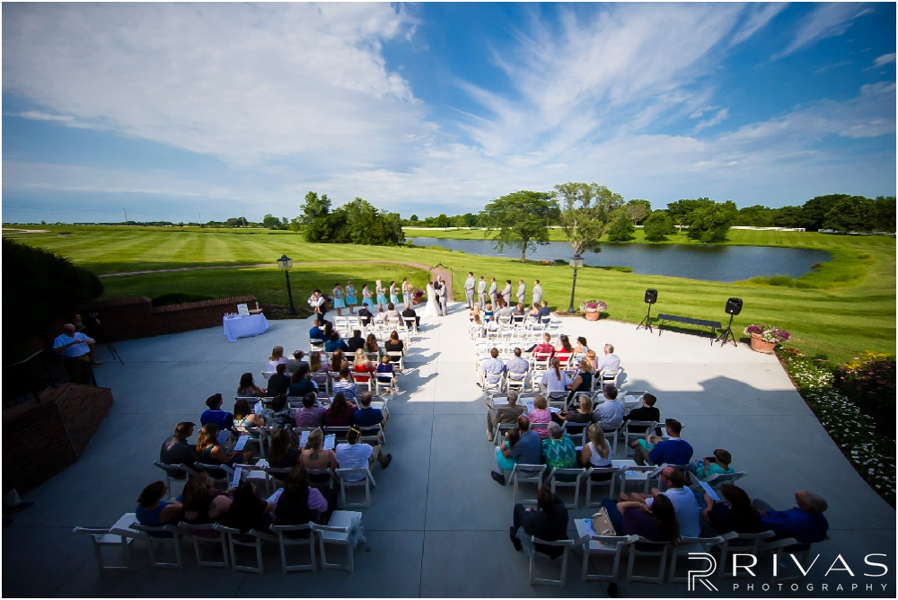 Mildale Farm Summer Wedding | A wide angle photo of a wedding ceremony taking place on the patio overlooking the pond during a summer wedding at Mildale Farm.