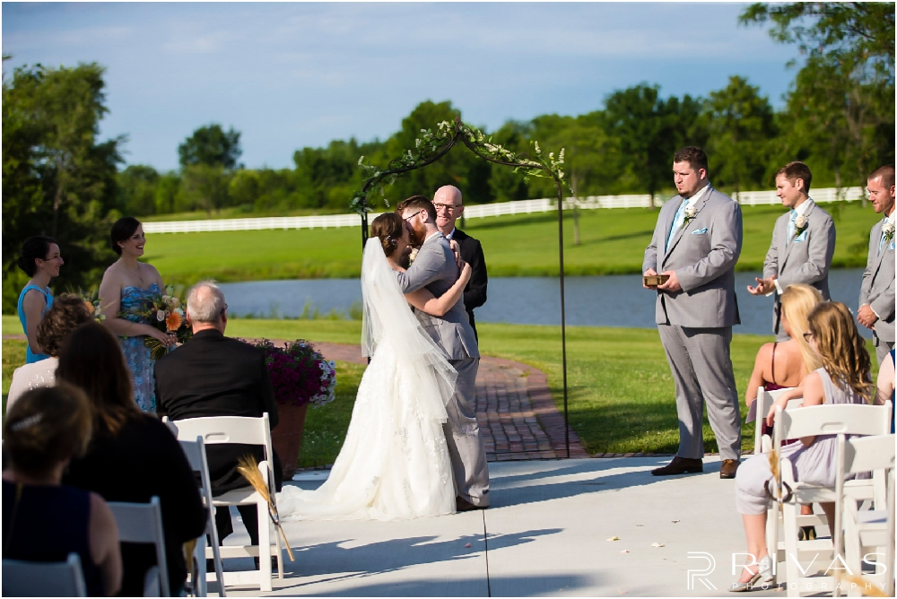 Mildale Farm Summer Wedding | A picture of a bride and groom sharing their first kiss at the end of their wedding ceremony on the patio at Mildale Farm.