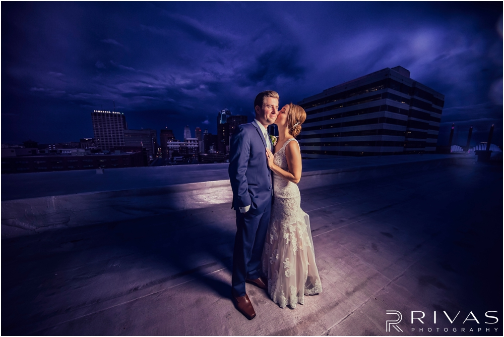 Rainy Wedding Day Sneak Peek | Dramatic portrait of a bride and groom embracing standing on the roof of The Garment House on Broadway in downtosn Kansas City under stormy skies after their wedding.