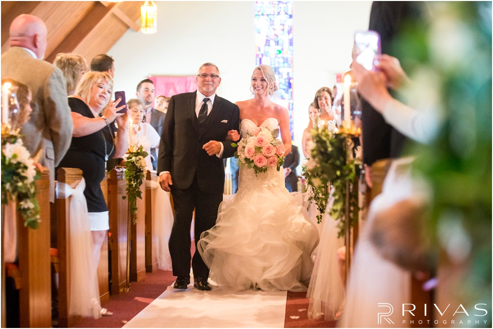 Staley Farms Golf Club Summer Wedding | A candid image of a bride's father walking her down the aisle during her wedding ceremony.
