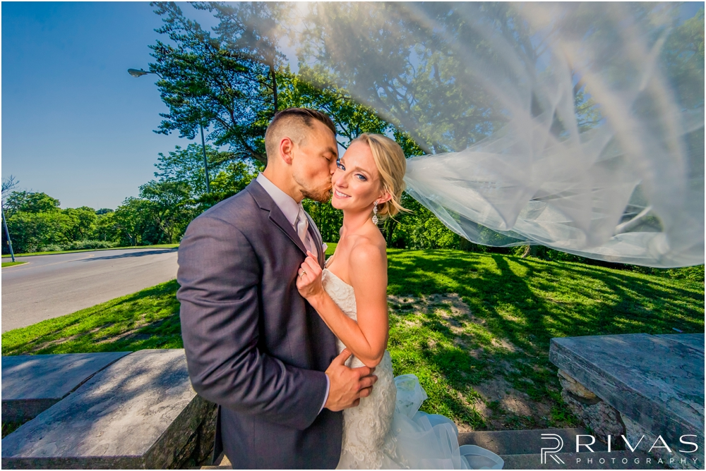 Staley Farms Golf Club Summer Wedding | A picture of a groom kissing his bride on the cheek as her veil blows in the wind after their wedding in Kansas City.