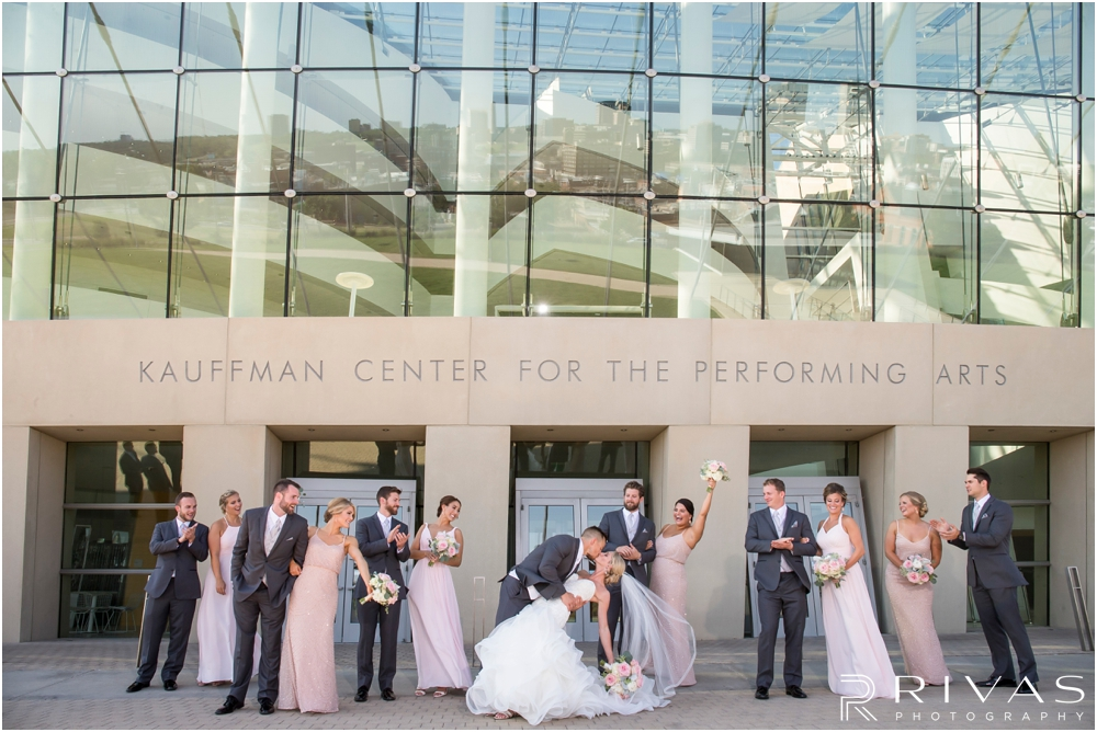 Staley Farms Golf Club Summer Wedding | A candid image of a groom dipping his bride with their wedding party at the Kauffman Center for the Performing Arts  after their wedding in Kansas City.