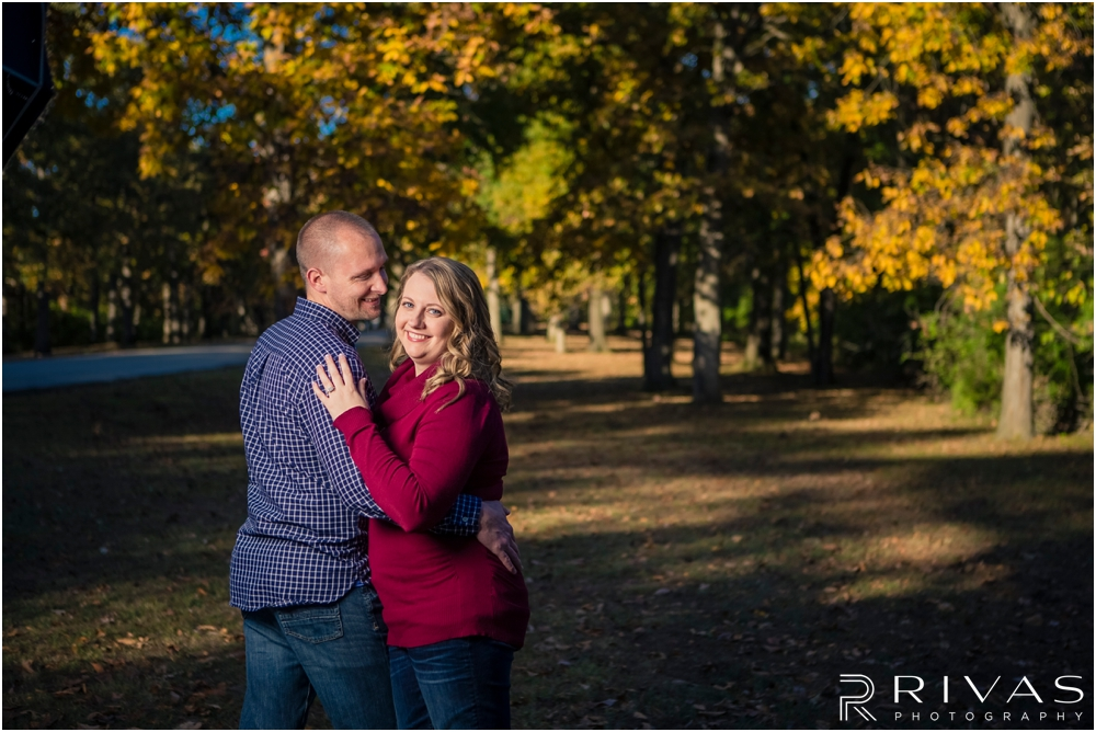Swope Park Engagement Session Sneak Peek | A photo of an engagement couple embracing, standing underneath yellow leaves on the tress in fall at Swope Park in Kansas City, MO.
