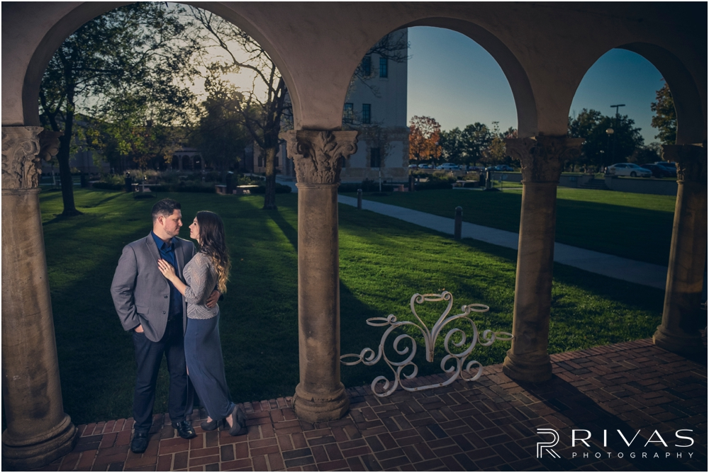 Unity Village Fall Engagement Sneak Peek | A dramatic picture of an engaged couple embracing while standing underneath a series of columns at Kansas City's Unity Village.