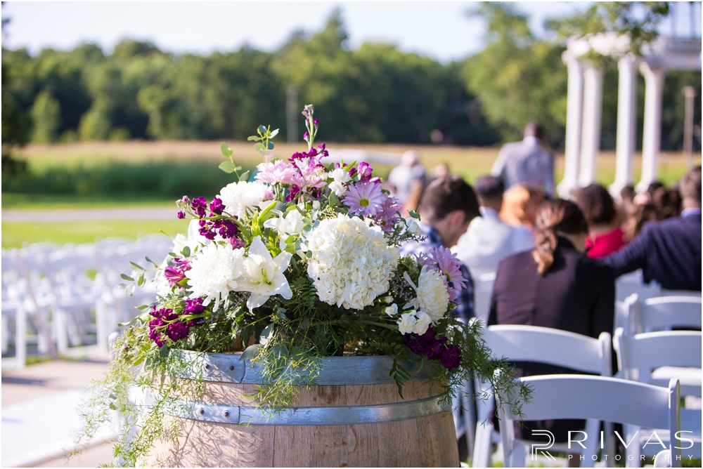Belvoir Winery Romantic Summer Wedding | A close-up photo of a floral arrangement decorating a wedding aisle on a wedding day at Belvoir Winery in Liberty, MO.