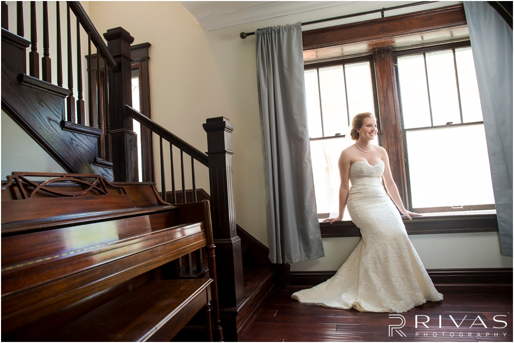 Classic Summer Wedding at Berg Event Space | A formal portrait of a bride sitting in a windowsill in her wedding gown on the morning of her wedding.