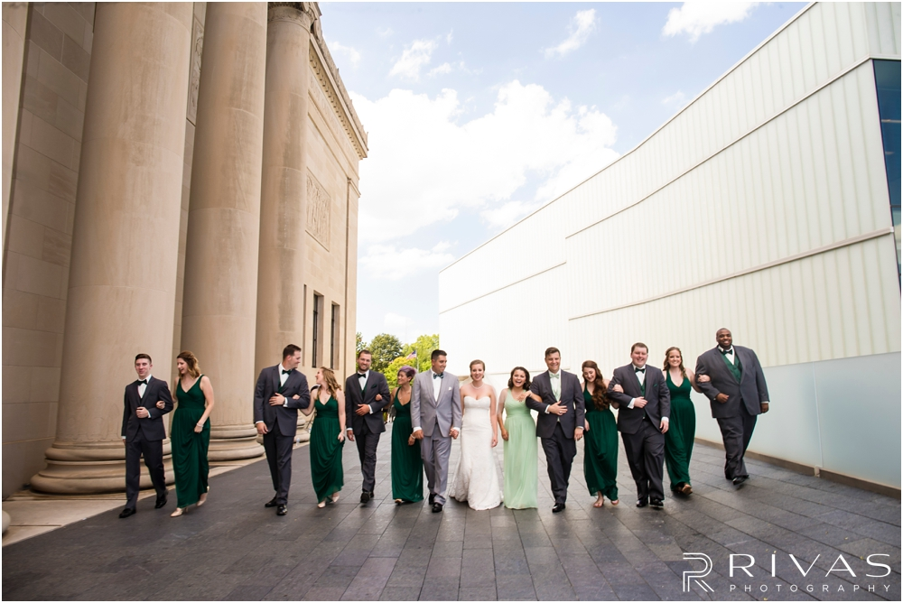 Classic Summer Wedding at Berg Event Space | A candid picture of a bride and groom with their wedding party walking arm in arm at The Nelson Atkins Museum of Art in Kansas City.