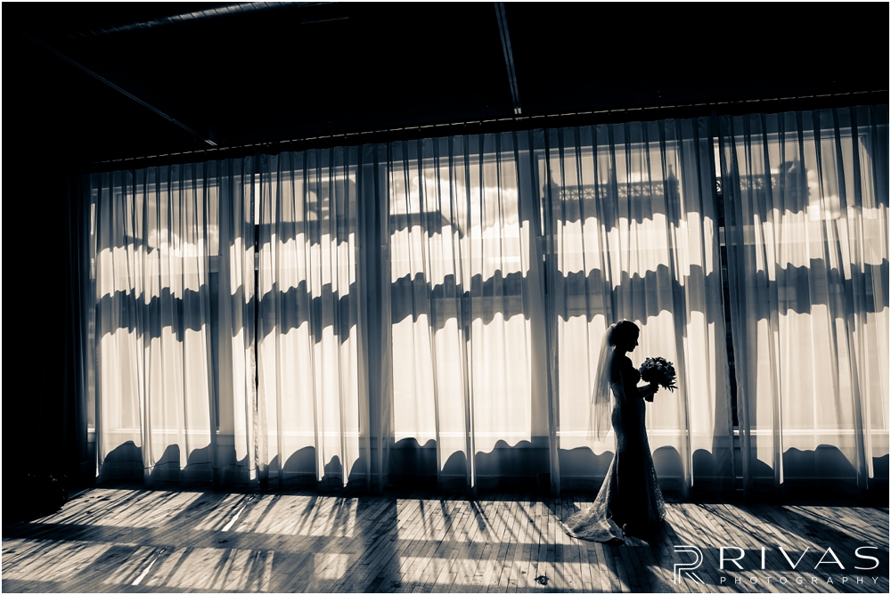 Classic Summer Wedding at Berg Event Space | A black and white silhouette portrait of a bride standing in front of the tall windows at Berg Event Space in Kansas City.