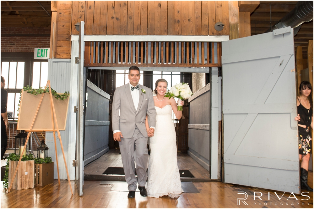 Classic Summer Wedding at Berg Event Space | A candid picture of a bride and groom entering their wedding reception at Berg Event Space in Kansas City.