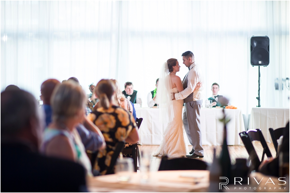 Classic Summer Wedding at Berg Event Space | A candid picture of a bride and groom sharing their first dance during their wedding reception at Berg Event Space in Kansas City.