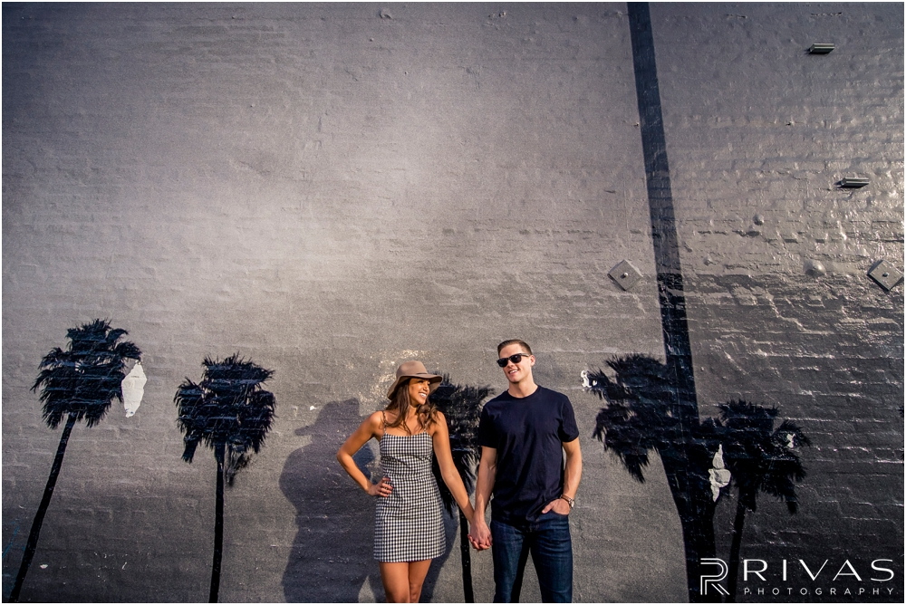 Venice Art Wall | A casual portrait of an engaged couple holding hands in front of a mural on the side of a building in Venice, California.
