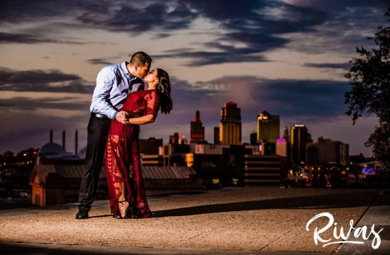 Stylish Kansas City Engagement Session | A photo of an engaged couple sharing a kiss in front of the Kansas City skyline as the man dips the woman during their sunset engagement session.