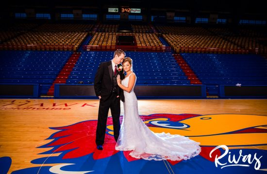 Fun Filled Wedding in Lawrence   Destination Wedding Photographers   A photo of a bride and groom sharing an embrace while standing barefoot on center-court of Allen Fieldhouse on their wedding day in Lawrence, Kansas.