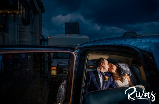 Stylish Scarritt Building Wedding | Kansas City Wedding Photographer | Rivas | A photo of a bride and groom sharing a kiss in the back of a classic car on their stormy wedding day in Kansas City.
