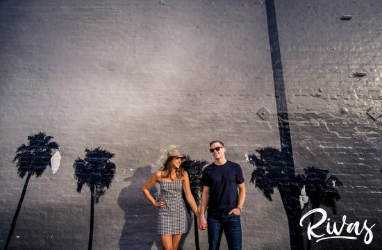 Venice Art Wall Sneak Peek | Destination Wedding Photographers | A candid image of an engaged couple holding hands and laughing together in front of a mural of palm trees in LA's Abbott Kinney Boulevar during their engagement session.