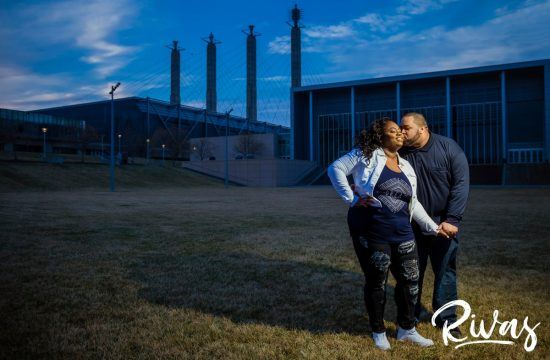 Downtown Kansas City Engagement Sneak Peek | Rivas | Kansas City Wedding Photographers | A photo of an engaged couple standing on the lawn of the Kansas City Convention Center with the four spires in the background during their evening engagement session.