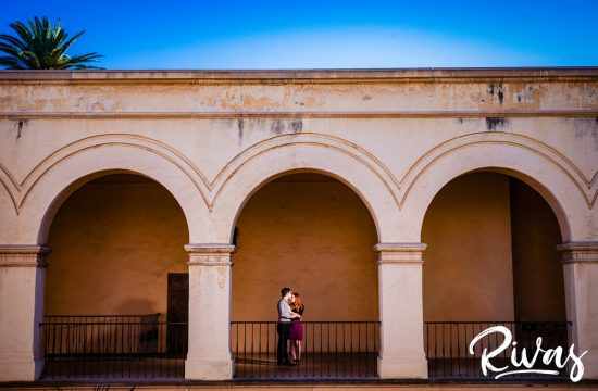 San Diego Destination Engagement Session | A portrait of an engaged couple sharing an embrace while standing underneath a series of arches with a peek of blue sky and palm tree above them.