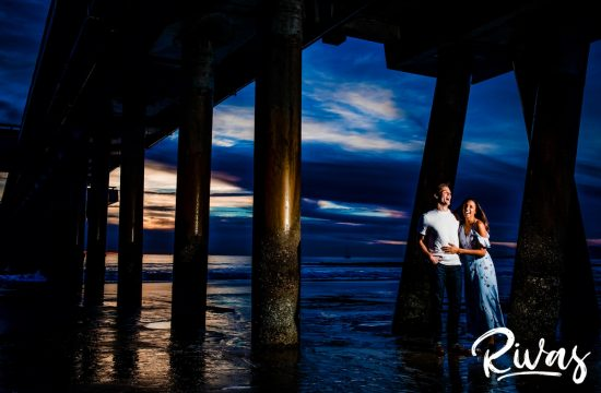 Vibrant Venice Engagement Session | A candid image of an engaged couple embracing and laughing while standing underneath the pier at Venice Beach.