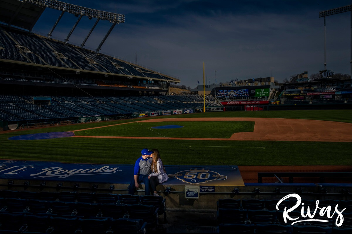 Spring Kauffman Stadium Engagement Pictures | A wide-shot of an engaged couple sitting on top of the Royal's dugout at Kauffman Stadium during their Kansas City Engagement Session.