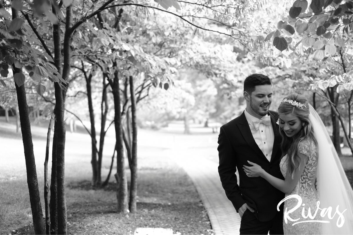 Elegant KC Wedding Sneak Peek | Kansas City Wedding Photographers | A black and white photo of a bride and groom embracing and laughing on their wedding day at Kansas City's Nelson Atkins Museum of Art.