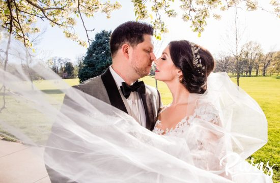 Spring Royal Room Wedding Reception | Kansas City Wedding Photographers | A photo of a bride and groom about to kiss while standing underneath a tree full of white blooms during their spring wedding day at Kansas City's Loose Park.