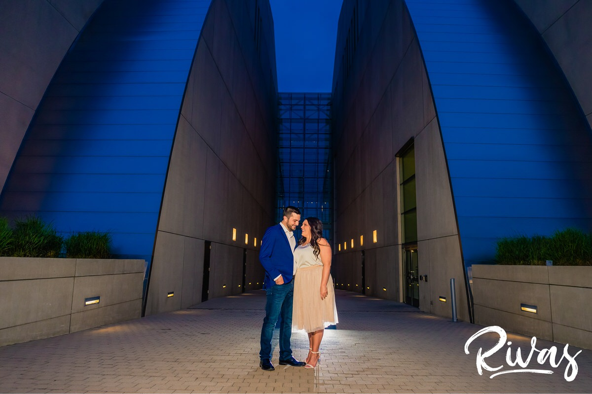 Summer Engagement Session Sneak Peek | Kansas City Wedding Photographers | A portrait of an engaged couple sharing an embrace while standing in front of Kansas City's Kauffman Center for the Performing Arts during their evening engagement session.