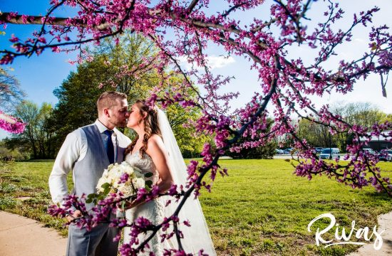 White and Navy Spring Wedding | Kansas City Wedding Photographers | A photo of a bride and groom embracing and sharing a kiss on their wedding day as the stand intertwined in a branch covered with purple buds at Shawnee Mission Park.