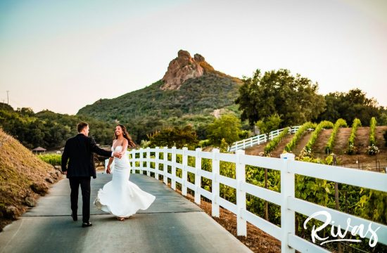 Romantic Vineyard Wedding Sneak Peek | Destination Wedding Photographers | A candid photo of a bride and groom dancing while walking down the road at Malibu's Saddlerock Ranch at sunset on the evening of their wedding.