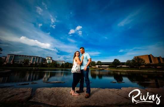 Summer Morning Session Sneak Peek | A vibrant photo of an engaged couple standing on a rock wall in front of a vibrant blue pond and sky near Kansas City's Plaza Neighborhood.