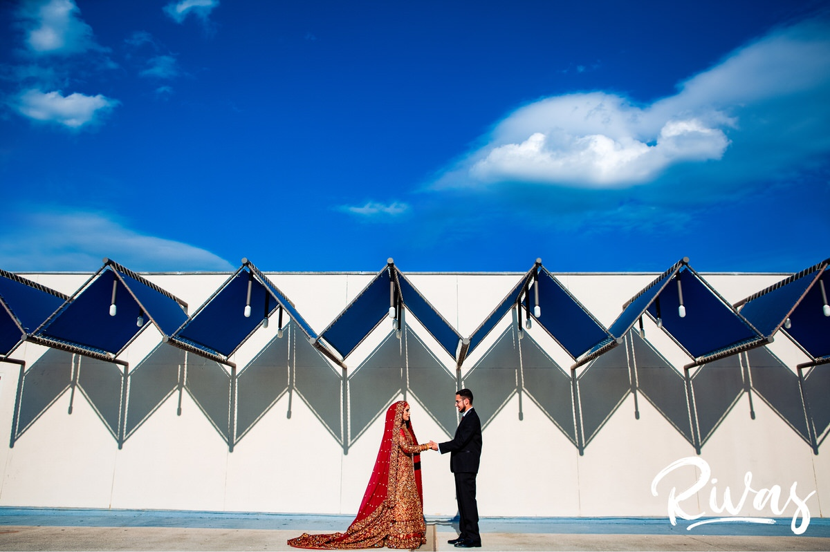 Westin Game Deck Bridal Session Sneak Peek | A formal portrait of an Indian bride and Iranian groom on their wedding day standing underneath a vibrant blue sky.
